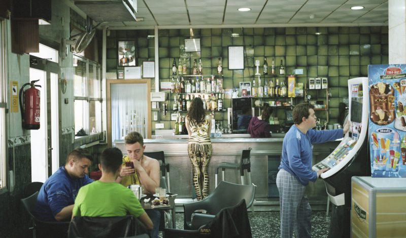 LA Kurzfilm DISCO RESPLANDECE © Chema García: Eine Bar, im Vordergrund 3 junge Männer an einem Tisch, rechts ein junger mann an einem Spielautomat, am Thresen eine junge Frau.