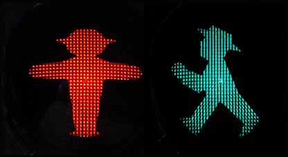Beitragsbild Checkliste für Online-Festival-Einreichungen: Ein rotes und ein grünes Ampelmännchen auf schwarzem Grund.
