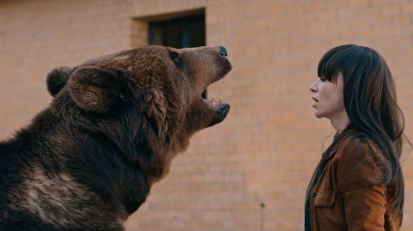 Film Berlin Metanoia: Eine junge Frau mit langen dunklen Haaren und brauner Jacke und ein Bär stehen sich gegenüber. Der Bär reißt das Maul auf. Sie wirkt ruhig.