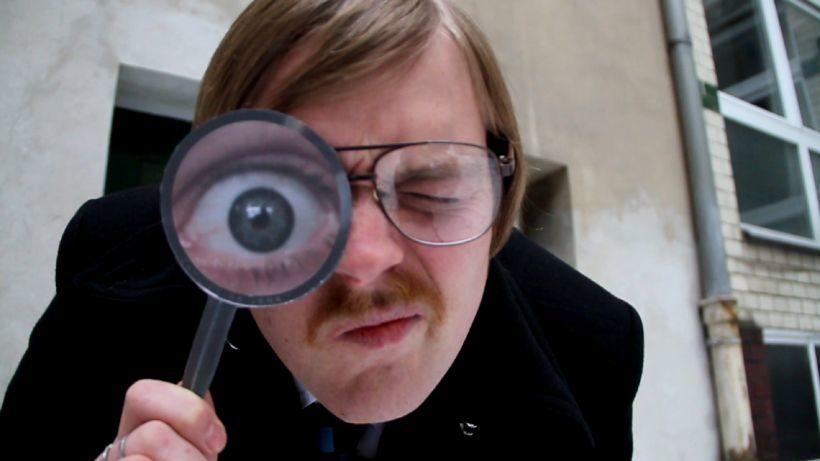 Kurzfilm Nun sehen Sie Folgendes von Erik Schmitt: ein Mann mit Brille und Schnurrbart schaut durch eine Lupe in die Kamera. Durch die Lupe wirkt sein rechtes Auge unnatürlich vergrößert.