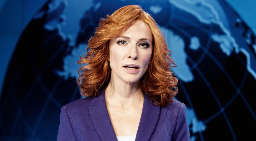 Eine Nachrichtensprecherin mit roten Haaren und blauem Kostüm, im Hintergrund eine Weltkugel in Blau und Schwarz als Studiodekoration.