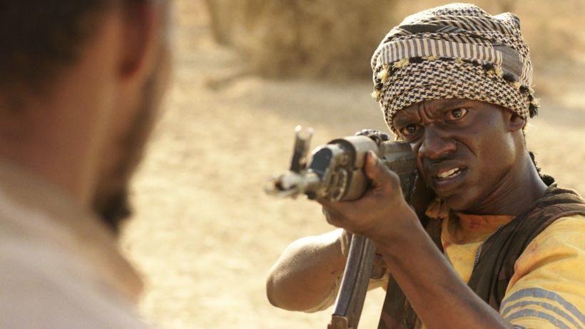 Ein schwarzer Mann mit einem Turban auf dem Kopf hält ein Gewehr im Anschlag. Er zielt auf einen anderen Mann, der im Vordergrund steht.