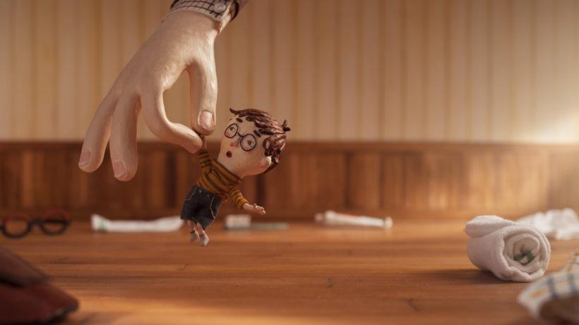 Ein Filmbild aus einem Animationsfilm: eine kleine Figur mit Brille, gestreiftem Pullover und kurzer Hose wird von einer sehr viel größeren Hand hochgehoben.