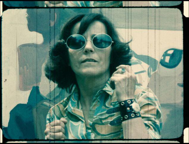 Ein Einzelbild aus einem Filmstreifen. Eine Frau mit gemusterter Bluse, Sonnenbrille und einem breiten Lederarmband schaut den Betrachter an.
