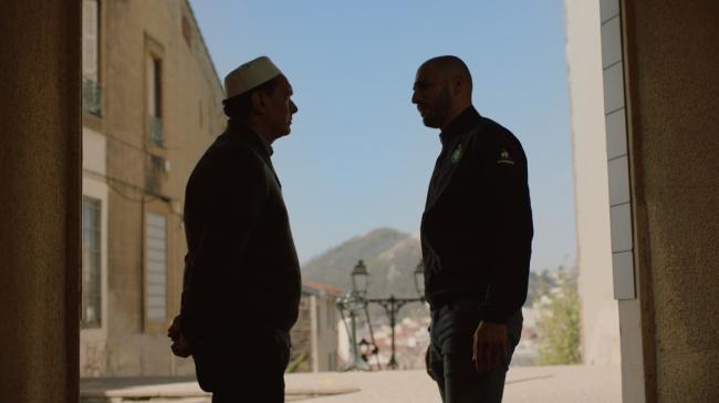Zwei Männer stehen in einer Gasse im Gegenlicht, einer trägt eine Kappe, im Hintergrund ist ein Berg zu sehen.