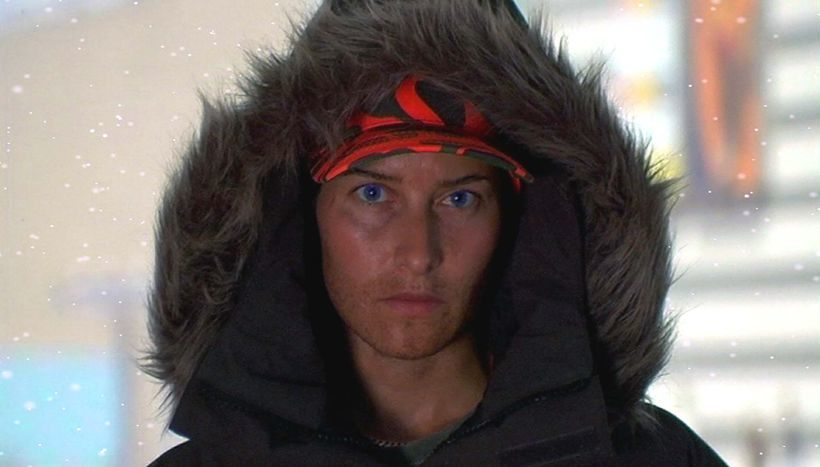 Ein junger Mann mit rot-schwarzer Kappe schaut in die Kamera. Er trägt eine Kapuze mit Fellbesatz