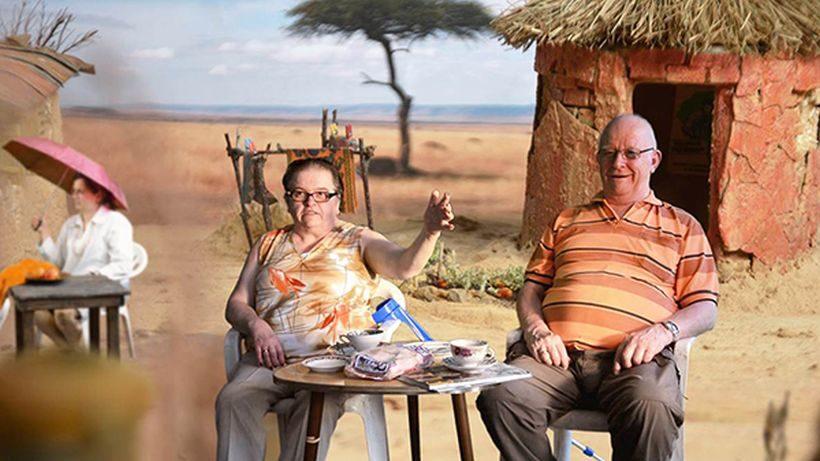 Ein Mann und eine Frau sitzen auf Gartenstühlen an einem kleinen Tisch, auf dem Tisch stehen Kaffeetassen. Im Hintergrund ist eine Wüstenlandschaft und eine Lehmhütte zu sehen.