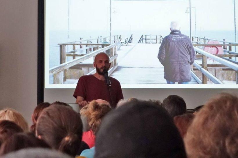 Beitragsbild für den Nachwuchstag KONTAKT der MDM: Ein junger Mann spricht vor Publikum, hinter ihm eine Leinwand, auf der ein Seebrücke zu sehen ist, darauf steht ein älterer Mann.