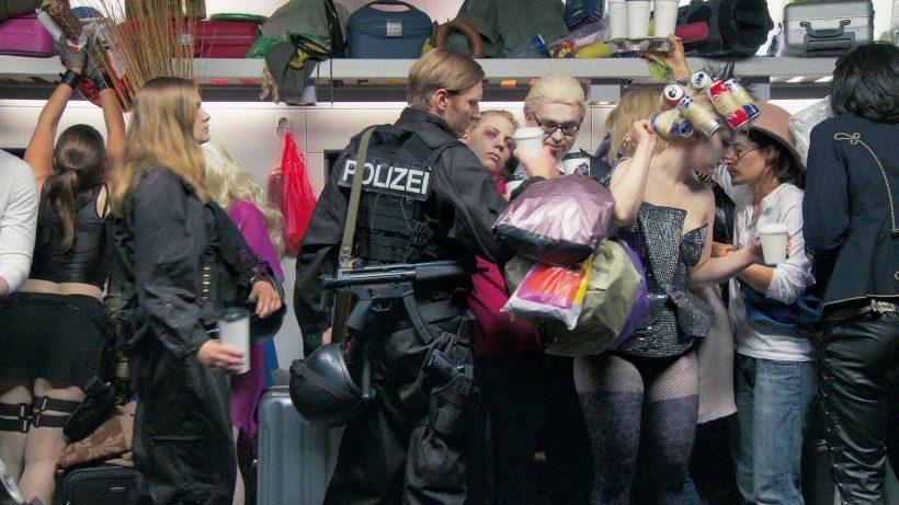 Filmstill SORRY: Ein überfüllter Zug, viele Menschen drängen sich in einem Wagon. Darunter ein Polizist und eine Polizistin sowie eine Frau in Corsage mit Lockenwicklern.