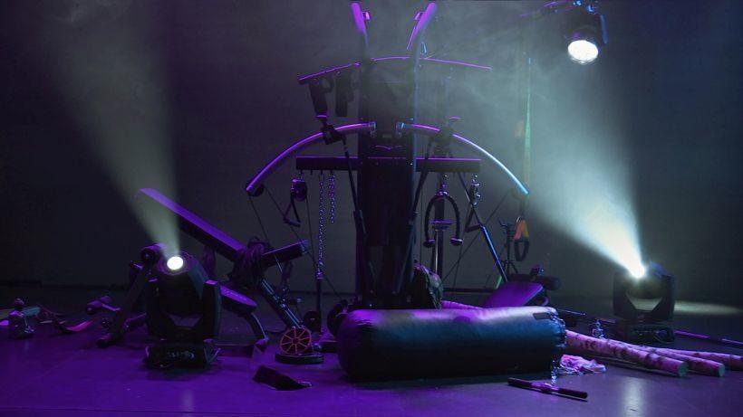 Filmstill NOCH EIN SPORTSTÜCK: ein Fitnessraum mit einer Vielzahl von Trainingsgeräten. Diese sind zu einer Skulptur angeordnen und werden von Scheinwerfern beleuchtet