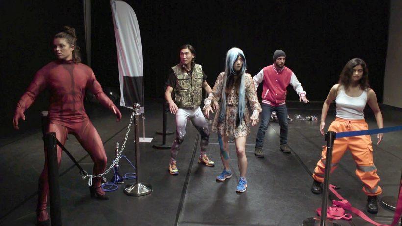 Film FREEROAM À REBOURS, MOD#I.1: 3 Frauen und 2 Männer stehen in einer starren Haltung in einem Raum. Vor ihnen teilweise Absperrungen.