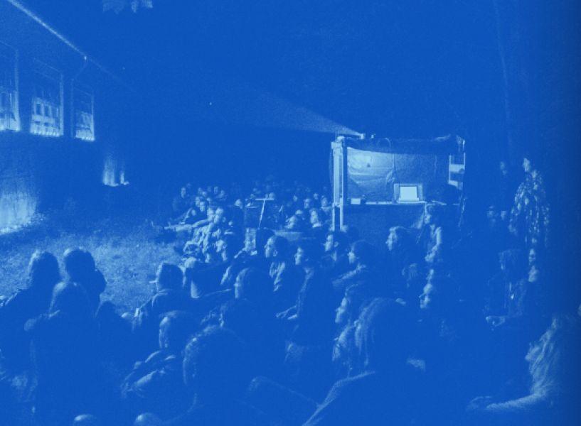Beitragsbild Kurzfilmwanderung: Eine Gruppe von Menschen sitzt auf einer Wiese und schaut einen auf eine Hauswand projizierten Kurzfilm.