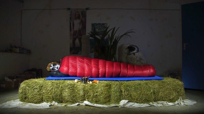 Film IF A STORECLERK GAVE ME TOO MUCH CHANGE: Eine schwarz-weiß geschminkte Gestalt liegt in einem roten Schlafsack auf einer Reihe Heuballen. Im Hintergunrd eine große Grünpflanze.