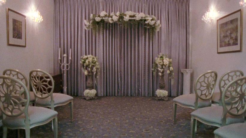 Filmstill DESERT MIRACLES: ein Blick in eine amerikanische Hochzeitskapelle, weiße Dekoration, Stühle und Blumen, zwei Bilder an den Wänden.