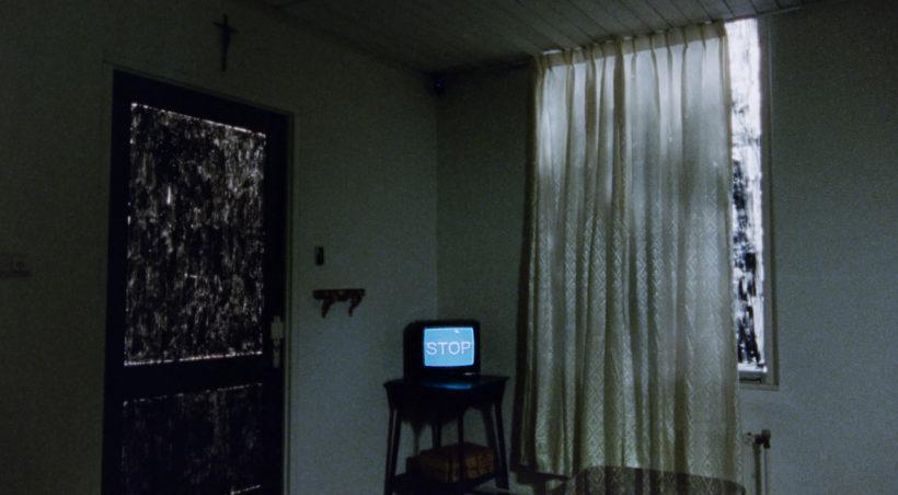 Filmstill ONE HOUR REAL: Ein abgedunkeltes Zimmer, zugezogene Vorhänge, im Zentrum ein alter Fernseher, auf dem das Wort STOP geschrieben steht.