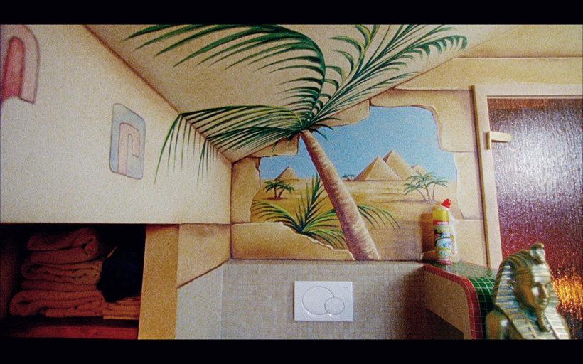 Filmstill SONNTAG BÜSCHERHÖFCHEN 2: ein Badezimmer mit ägyptischer Dekoration - ein Bild von Pyramiden, eine Palma, eine Pharao-Büste. Im Hintergrund ein WC-Reinigungsmittel.