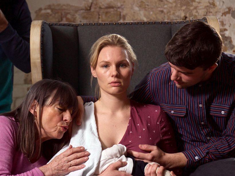 Filmstill KLEPTOMAMI - Eine junge Frau mit blonden Haaren sitzt in einem Sessel und stillt ein Baby. Ihr Blick ist leer. Der Kopf des Babys ist von einem weißen Tuch verdeckt. Eine ältere Frau und ein junger Mann sitzen daneben und berühren das Kind