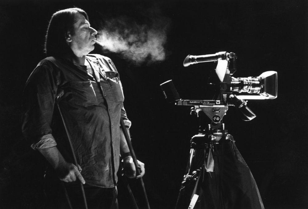 Eine schwarz-weiß-Aufnahme: ein Mann mit Gehhilfen unter beiden Armen und Zigarette im Mund steht neben einer Filmkamera.