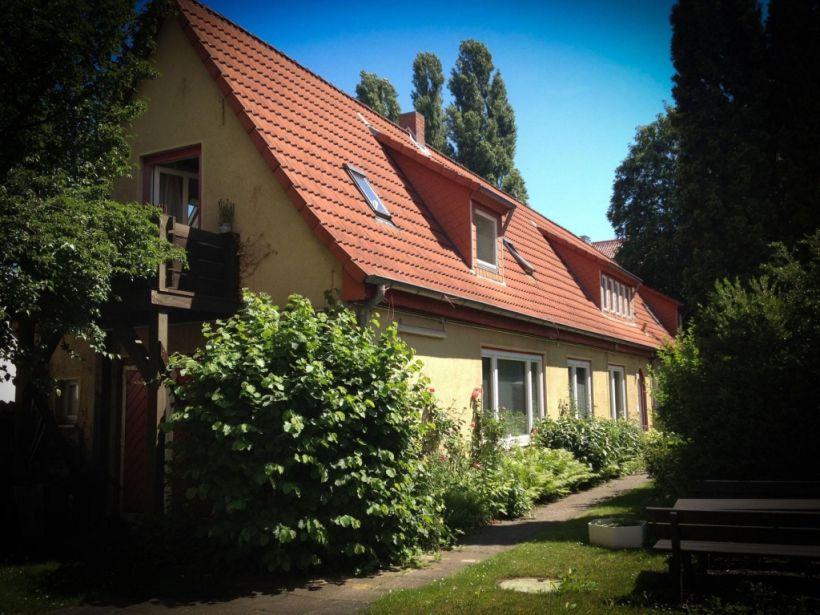 Beitragsbild Cast & Cut Stipendium: ein gelbes Haus mit rotem Ziegeldach, rundherum Bäume, blauer Himmel