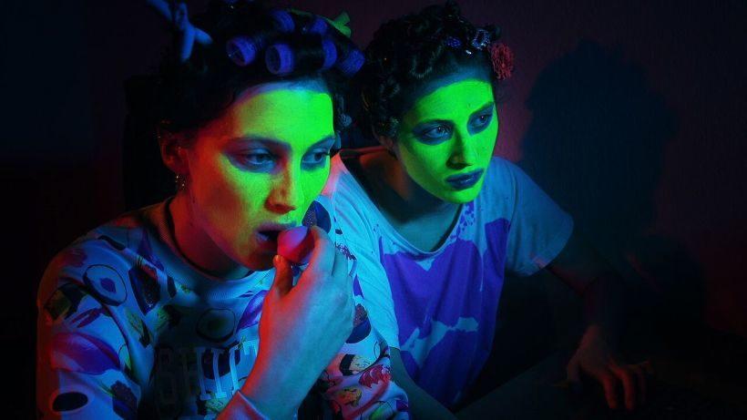 Filmstill CALL OF BEAUTY: zwei junge Frauen im Halbdunkel, leicht bläuliches Licht. Sie tragen Gesichtsmasken und Lockenwickler, sie schauen auf Computer-Monitore. Die linke der beiden schminkt sich die Lippen.
