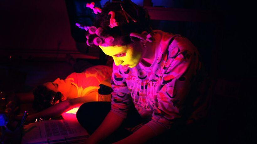 Filmstill CALL OF BEAUTY: zwei junge Frauen im Halbdunkel - eine im Vordergrund, ihr Gesicht ist mit einer gelben Gesichtsmaske bedeckt, sie trägt einen pinkfarbenen Pullover und Lockenwickler, sie schaut auf einen Computer-Monitor. Die andere Frau liegend im Hintergrund.