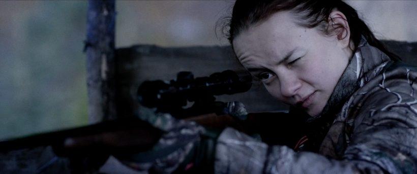 Filmstill RÅ: Ein junges Mädchen hält eine Jagdwaffe im Anschlag, sie schaut durch das Zielfernrohr. Das linke Auge ist zugekniffen.