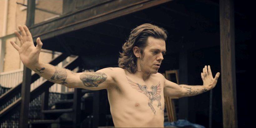 Filmstill JOE BOOTS: Ein etwas 30jähriger Mann mit langen Haaren und freiem Oberkörper breitet die Arme aus und schaut nach rechts aus dem Bild heraus, er hat mehrere auffällige Tatoos.