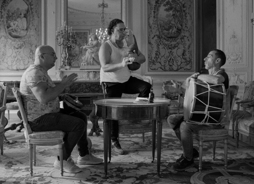Ein Bild in schwarz-weiß. Drei Musiker in einem barocken Raum, zwei Trommler sitzend, ein Dudelsackspieler stehend an einem runden Tisch.