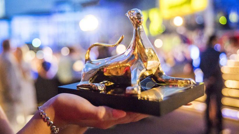 eine Frauenhand hält die Preisstatue des Locarno Film Festivals - einen liegenden goldenen Leoparden